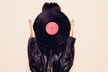 Faceless Woman In Leather Jacket Hiding Face Behind Vinyl Record In Studio On Pink Background