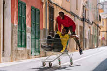 Happy Carefree Young African American Friends In Casual Clothes Riding Around In Shopping Trolley In Street
