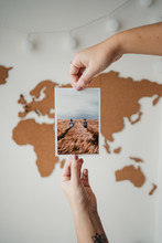 Crop Unrecognizable Female Holding Postcard In Front Of Wall World Map At Home In Paris
