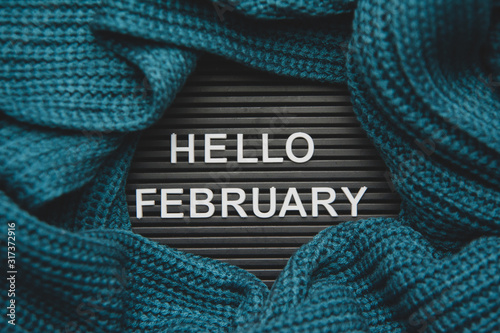 Fototapeta Hello February - text on a letter board with a knitted green-blue, warm, cozy scarf. Winter concept obraz