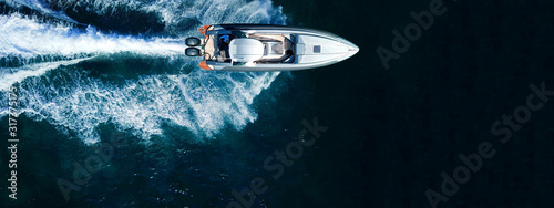 Fototapeta Aerial drone top down ultra wide photo of inflatable speed boat cruising in high speed in deep blue Aegean sea obraz na płótnie