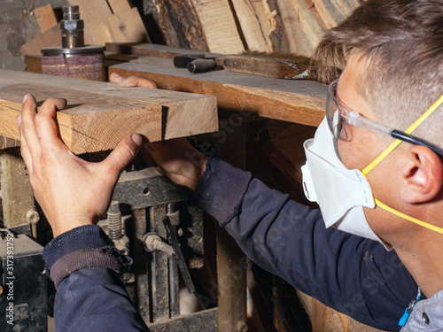 Obraz a guy a carpenter, a craftsman in a respirator and construction glasses, selects wooden boards for and processing the blanks of his products. woodworking concept  - fototapety do salonu
