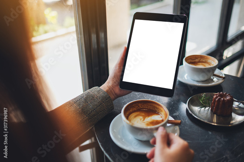 Obraz Mockup image of a woman sitting and holding black tablet pc with blank white desktop screen while drinking coffee in cafe - fototapety do salonu