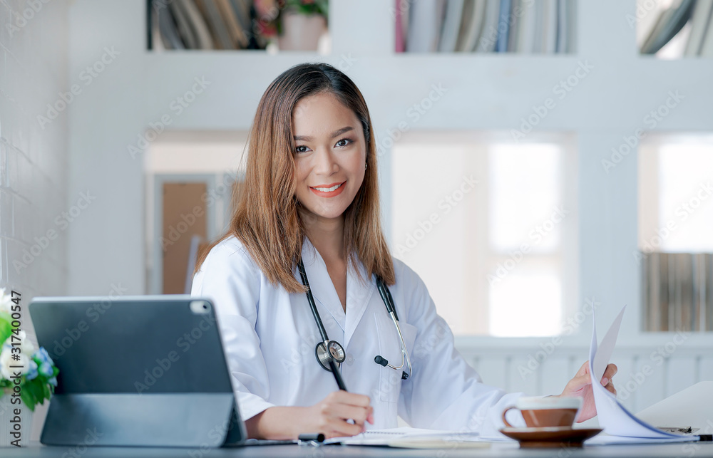 Fototapeta Young female doctor working at office desk, smiling and looking at camera.