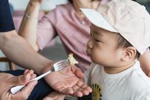 Little Asian Boy Eating Bread