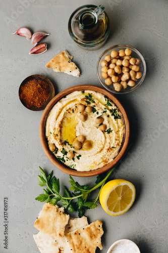 Fototapeta Large bowl of homemade hummus garnished with chickpeas, red sweet pepper, parsley and olive oil obraz