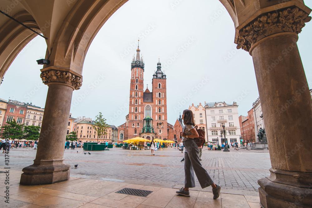 Obraz tourist woman at central krakow market square copy space fototapeta, plakat