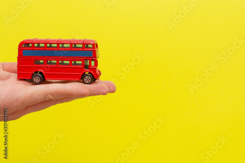British toy double-decker red bus holding by male hand on yellow background with copy space for your text Fototapet