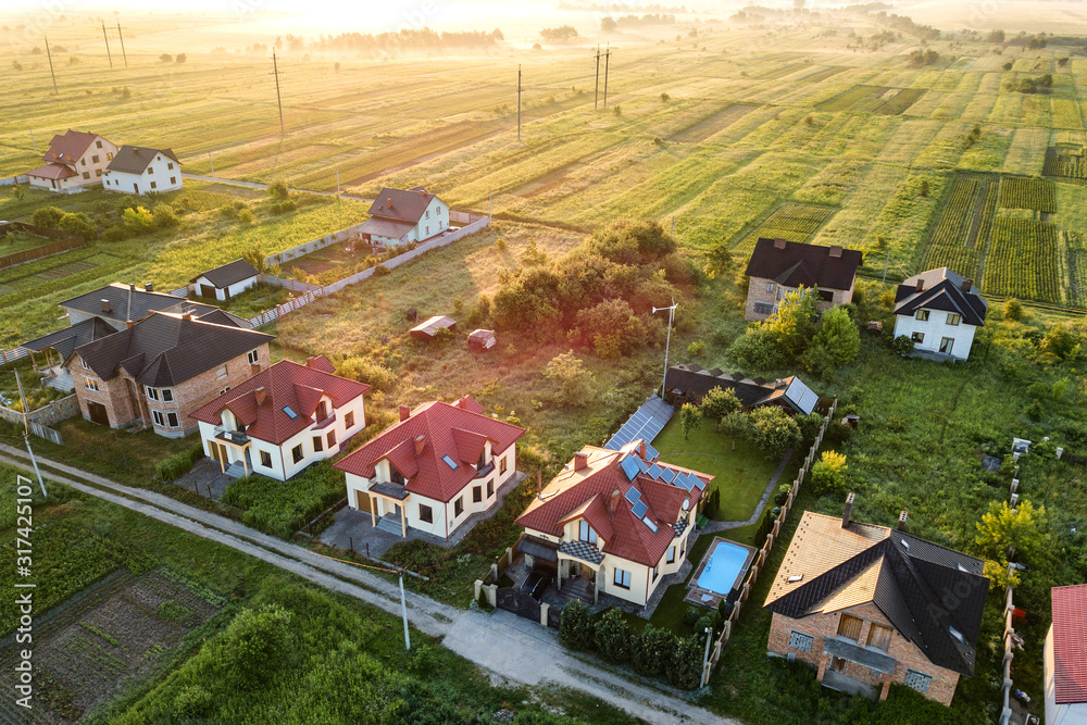 Fototapeta Aerial view of rural residential area with private homes between green fields at sunrise.