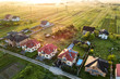 Aerial view of rural residential area with private homes between green fields at sunrise.