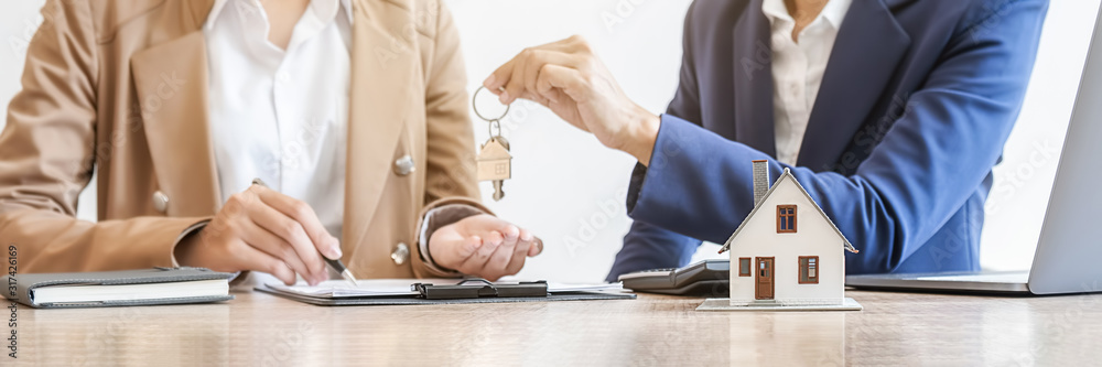 Fototapeta Real estate agent holding a key and asking costumer for contract to buy, get insurance or loan real estate or property.