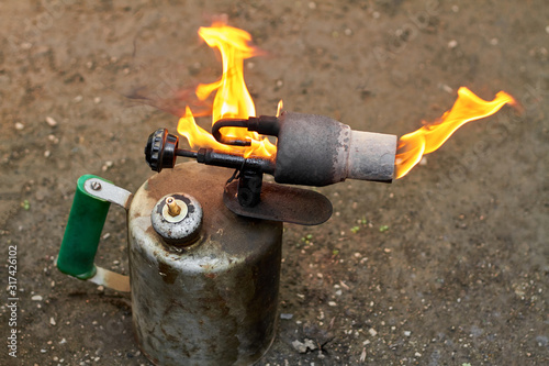 Photo Old rusty blowtorch with fire.