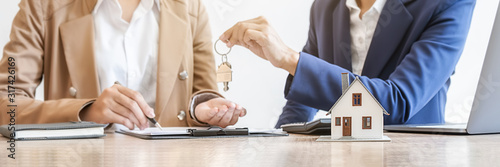 Fototapeta Real estate agent holding a key and asking costumer for contract to buy, get insurance or loan real estate or property. obraz