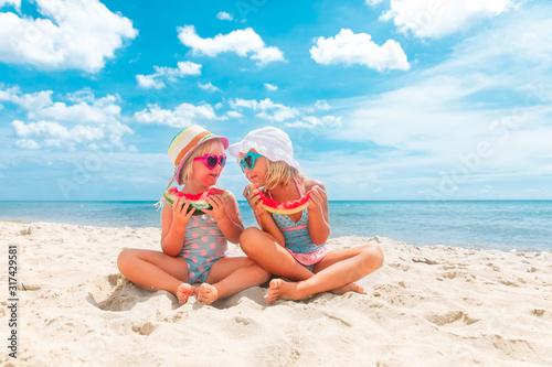 Canvastavla happy little girls eating watermelon at beach