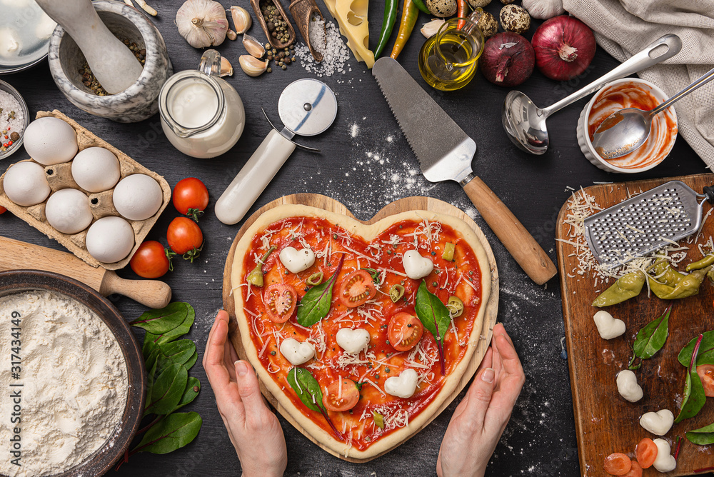 Fototapeta woman preparing a festive dinner for two in honor of Valentine's Day classic Italian pizza Margherita in the shape of a heart and mozzarella in the shape of a heart