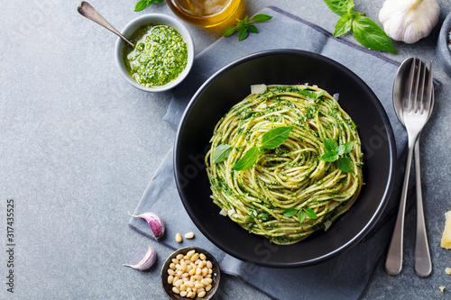 Fototapeta Pasta spaghetti with pesto sauce and fresh basil leaves in black bowl
