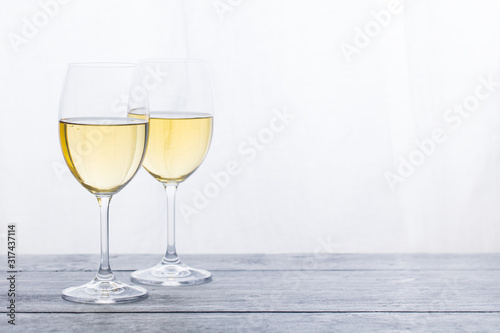 Fototapeta Two glasses with white wine on grey wooden background. Copy space. obraz