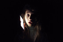 Child Girl With A Phone In The Dark. Frightened Child Calls To Mother: Power Outage.