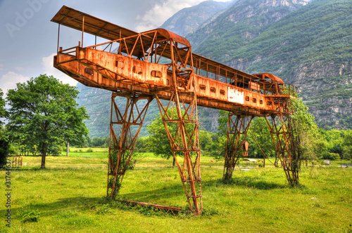 Rusty Gantry Crane on the Green Field with Mountain in Switzerland Canvas Print