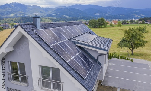 High angle shot of a private house situated in a valley with solar panels on the Canvas-taulu