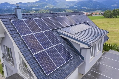 Obraz High angle shot of a private house situated in a valley with solar panels on the roof - fototapety do salonu