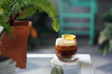 Iced Coffee With Orange - A Glass Of Espresso Shot Mixed With Craft Soda And Orange Juice And Topped With Rosemary Leaves On Blurred Background.
