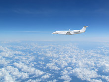 White Private Jet Business Jet Flies Against Backdrop Of Beautiful White Clouds On Blue Sky
