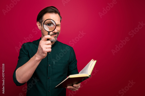 Fotografie, Obraz Photo of concentrated focused man looking at you through loupe using book to exa