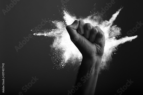 Raised clenched fist with white powder explosion, power, protest concept Canvas Print
