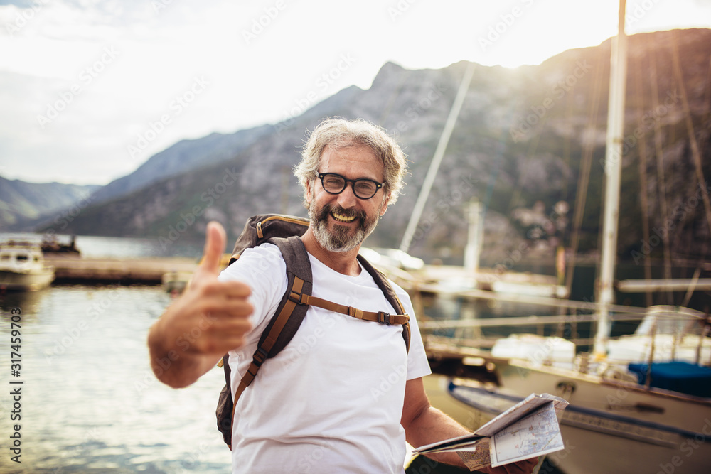 Fototapeta Smiling tourist mature man standing with map and backpack near the sea.