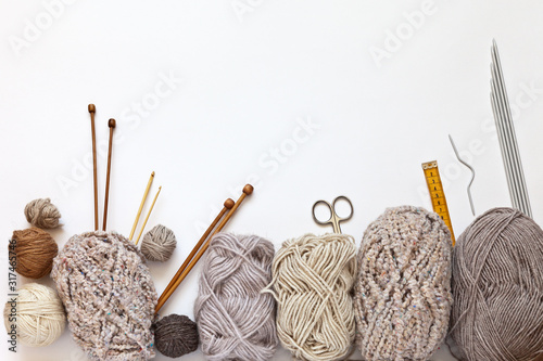 Photo Accessories for hand knitting and balls of woolen yarn in beige colors on a white background