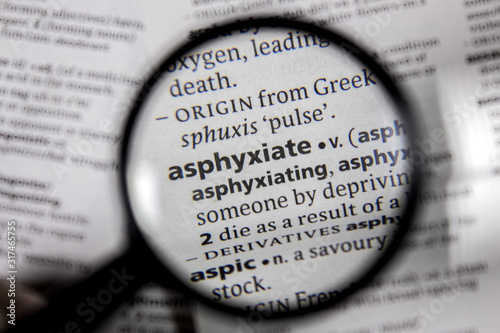 Photo The word or phrase asphyxiate in a dictionary.