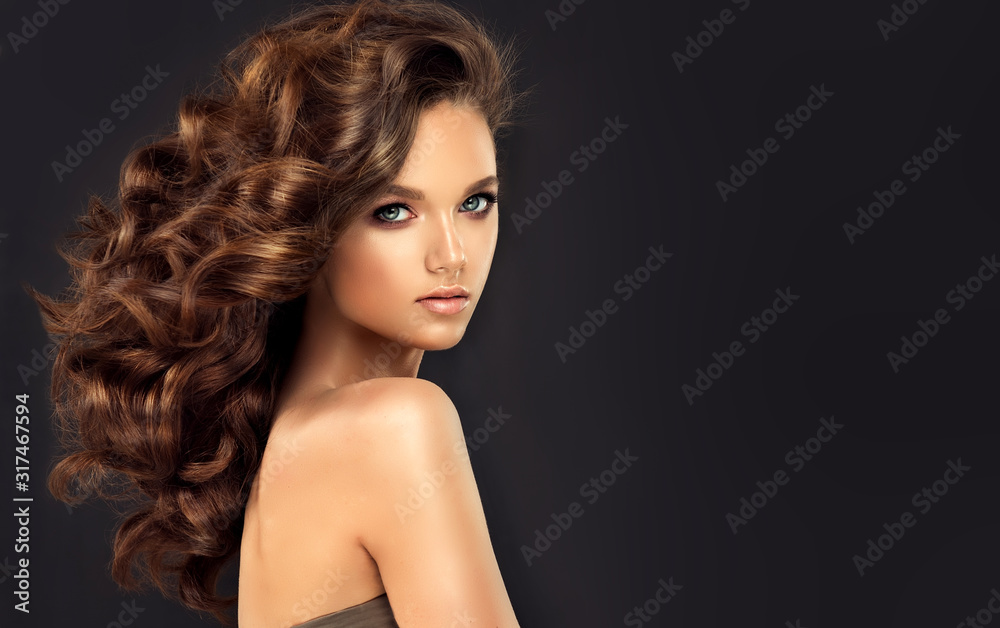 Fototapeta Beauty brunette girl with long  and   shiny wavy black hair .  Beautiful   woman model with curly hairstyle .