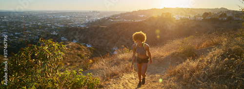 athletic african american woman hiking up runyon canyon trail at sunset Obraz na płótnie