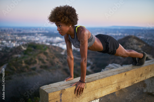 Fototapeta athletic african american woman working out doing pushups on bench at runyon canyon obraz