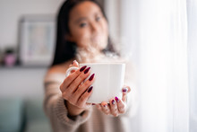 Cup Of Tea Or Coffee In Hand Of Asian Woman At Home
