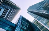 Wieżowce London Docklands. Niski, szeroki kąt widzenia zbiegających się współczesnych wieżowców ze szkła i stali.