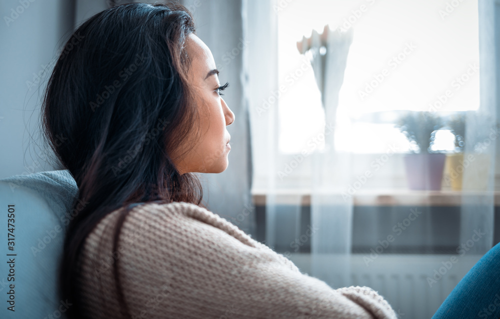 Fototapeta Depressed asian girl sitting on sofa at home and thinking