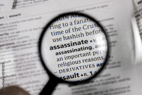 Photo The word or phrase assassinate in a dictionary.