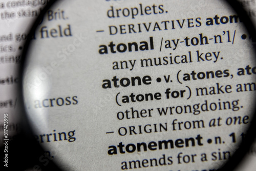 Photo The word or phrase atone in a dictionary.