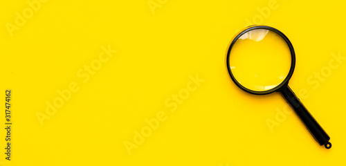 Close up magnifier glass on yellow background. View from above. Canvas-taulu