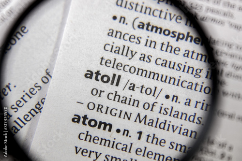 Photo The word or phrase atoll in a dictionary.