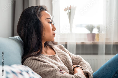 Fototapeta Sad asian girl sitting on sofa at home and thinking obraz