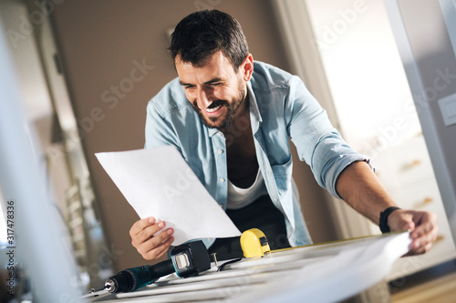 Man reading instructions for assembling baby crib. Canvas Print
