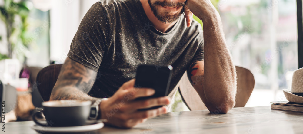 Fototapeta Handsome bearded hipster man use smartphone with coffee at table in cafe.Communication and technology concept