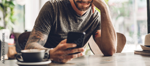 Fototapeta Handsome bearded hipster man use smartphone with coffee at table in cafe