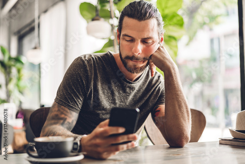 Tela Handsome bearded hipster man use smartphone with coffee at table in cafe