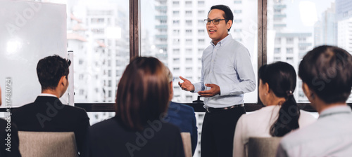 Businessman standing in front of group of people in consulting meeting conference seminar at hall or seminar room.presentation and coaching concept - 317480724