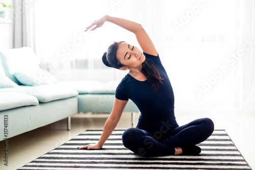 Fototapeta Young asian girl exercising at home on carpet in living room obraz