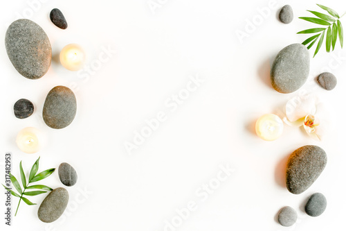 Spa stones, palm leaves, flower white orchid, candle and zen like grey stones on white background Wallpaper Mural
